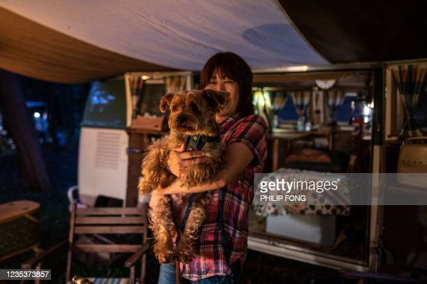 This picture taken on September 19, 2021 shows campervan enthusiast Junko Yanagawa hugging her dog Luck in front of a Volkswagen Type 2 at a campsite...