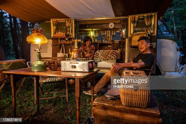 This picture taken on September 19, 2021 shows campervan enthusiast Junko Yanagawa , Yoshinori Yanagawa and their dog Luck sitting in front of a...