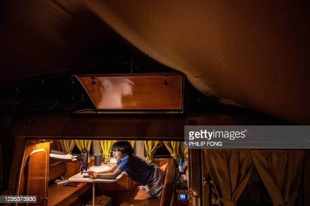 This picture taken on September 19, 2021 shows campervan enthusiast Takayuki Minagawa making dinner as his son Rintaro Minagawa watches a video on a...