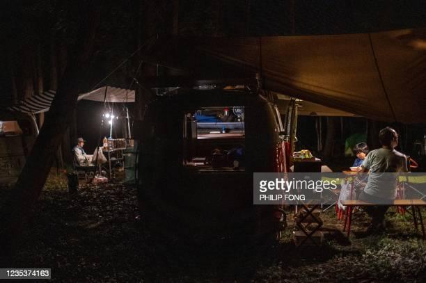 This picture taken on September 19, 2021 shows campervan enthusiast Takayuki Minagawa having dinner with his son Rintaro Minagawa next to a 1964...