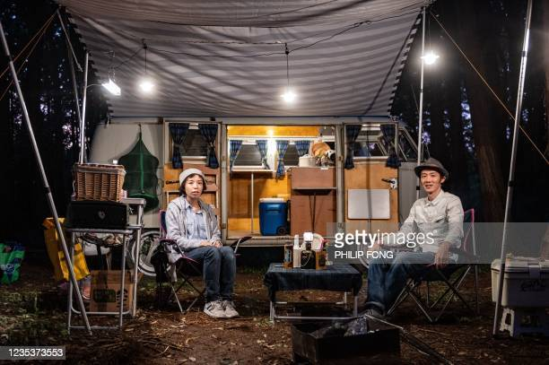 This picture taken on September 19, 2021 shows campervan enthusiasts Hayato Simogawa and Ayako Simogawa sitting in front of a 1965 Volkswagen Type 2...