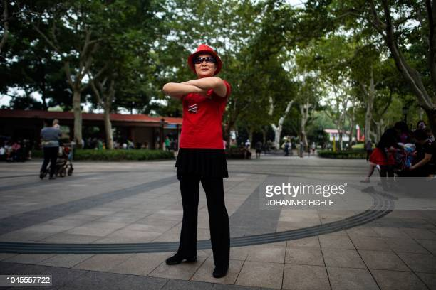 This picture taken on September 2 2018 shows a woman from a square dancing team striking a pose for a photograph in a public park in Shanghai In a...