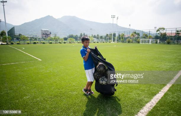 This picture taken on September 21 2018 shows a boy carrying a net of balls after a training session at the Guangzhou RF Football Academy in Meizhou...