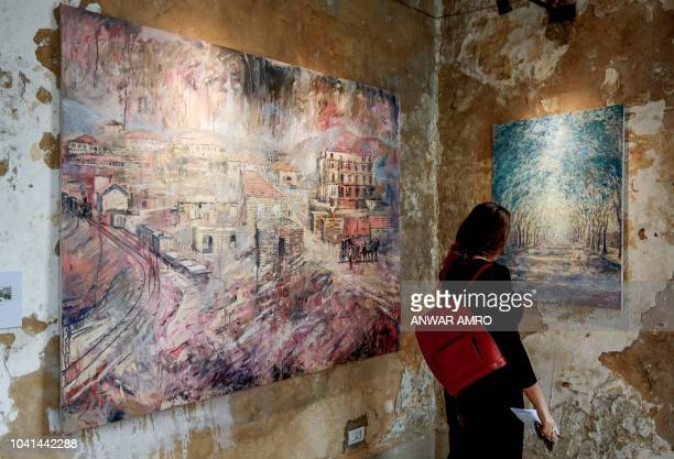 This picture taken on September 21 2018 shows a visitor viewing paintings by 45yearold British artist Tom Young during an exhibition at the Sofar...