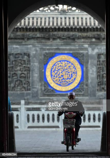 This picture taken on September 22 2015 shows a Chinese Hui Muslim arriving for evening prayers on a motorbike at the Great Mosque of Tongxin located...