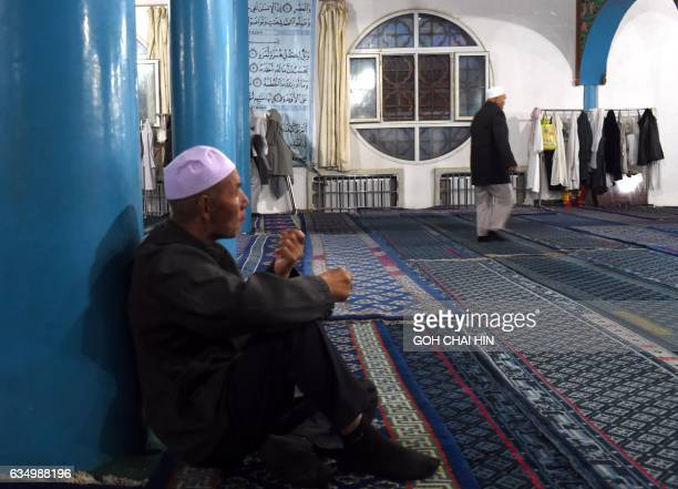 This picture taken on September 22 2015 shows Chinese Hui Muslim men during evening prayers at the Great Mosque of Tongxin located some 200 kms from...