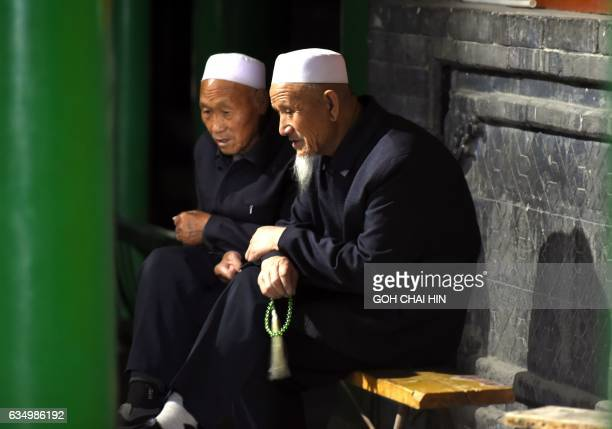 This picture taken on September 22 2015 shows two Chinese Hui Muslims chatting after evening prayers at the Great Mosque of Tongxin located some 200...