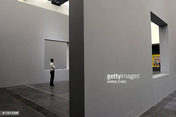 This picture taken on September 22 2016 shows a staff member at the Parcours Zeng Fanzhi exhibition at Beijing's Ullens Centre for Contemporary Art...
