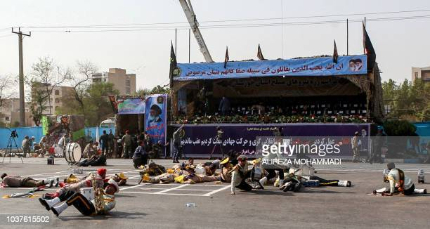 This picture taken on September 22 2018 in the southwestern Iranian city of Ahvaz shows injured soldiers lying on the ground at the scene of an...