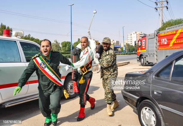This picture taken on September 22 2018 in the southwestern Iranian city of Ahvaz shows an Iranian soldier carrying an injured comrade at the scene...