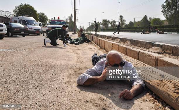 This picture taken on September 22 2018 in the southwestern Iranian city of Ahvaz shows people and soldiers lying on the ground for cover at the...