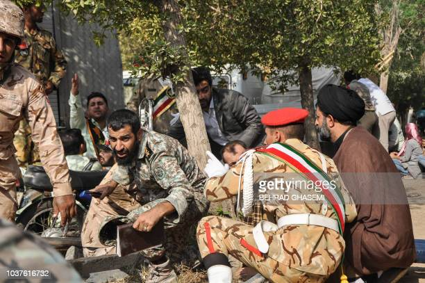 This picture taken on September 22 2018 in the southwestern Iranian city of Ahvaz shows soldiers and a Shiite Muslim cleric sitting close to the...