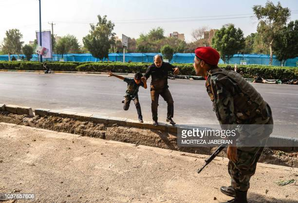 This picture taken on September 22 2018 in the southwestern Iranian city of Ahvaz shows a man and a boy running off a street onto the curb as an...
