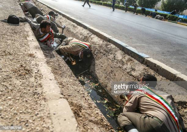 This picture taken on September 22 2018 in the southwestern Iranian city of Ahvaz shows Iranian soldiers taking cover in a rain gutter off a street...