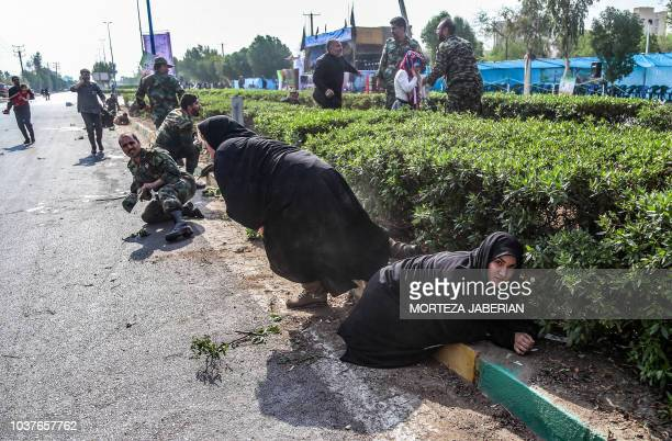 This picture taken on September 22 2018 in the southwestern Iranian city of Ahvaz shows Iranian women and soldiers taking cover next to bushes at the...