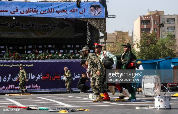 This picture taken on September 22 2018 in the southwestern Iranian city of Ahvaz shows Iranian soldiers carrying away an injured comrade at the...