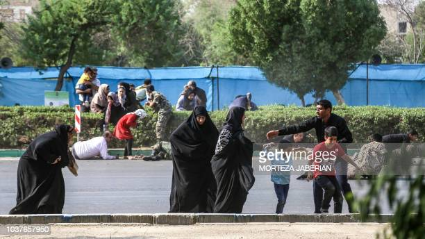 This picture taken on September 22 2018 in the southwestern Iranian city of Ahvaz shows a man helping women and children as they try to flee at the...