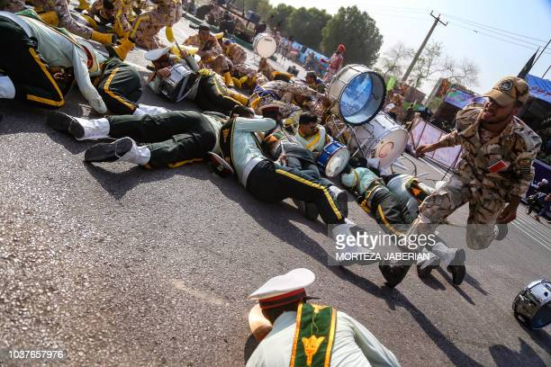 TOPSHOT This picture taken on September 22 2018 in the southwestern Iranian city of Ahvaz shows a soldier running past injured comrades lying on the...