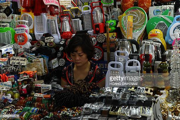 This picture taken on September 23 2014 shows a vendor sitting at her stall full of Chinesemade consumer goods at Dong Kinh market in the northern...