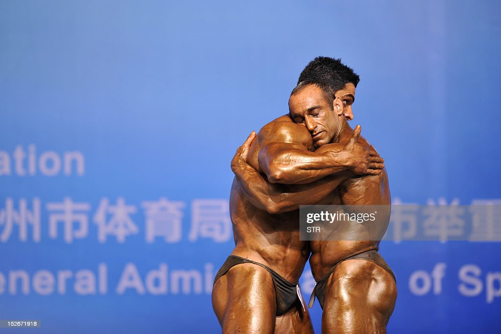 This picture taken on September 23, 2012, shows two competitors hugging each other during the 46th Asian Bodybuilding and Physique Sports Championships in Guangzhou, in southern China's Guangdong province. Over 200 athletes from more than 20 Asian countries signed up for the games, and champions from other competitions also joined in to show off their muscles. CHINA