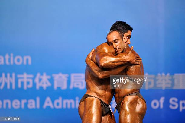 This picture taken on September 23 shows two competitors hugging each other during the 46th Asian Bodybuilding and Physique Sports Championships in...