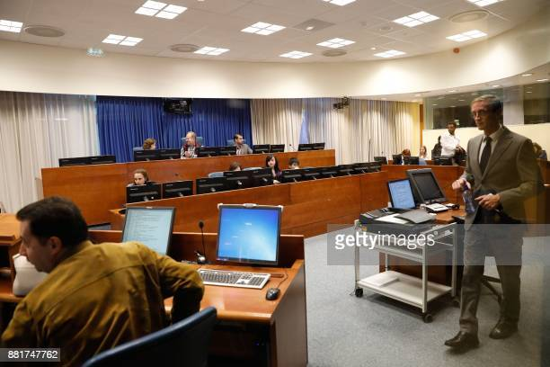 This picture taken on September 24 2017 shows people walking and sitting in a courtroom of the International Criminal Tribunal for the former...