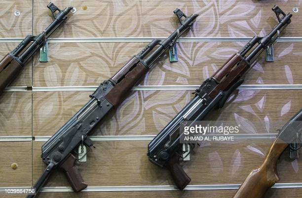 This picture taken on September 24, 2018 shows an assortment of Kalashnikov assault rifles hanging on the wall of a licenced arms shop in the Iraqi...