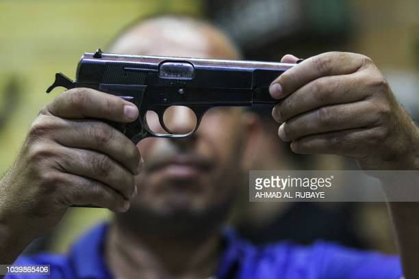 This picture taken on September 24 2018 shows an Iraqi inspecting a pistol at a licenced arms shop in the Iraqi capital Baghdad's eastern Sadr City...