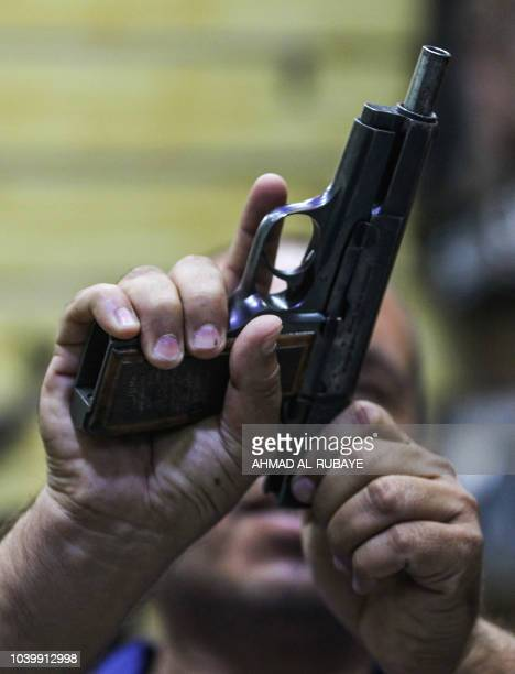 This picture taken on September 24 2018 shows an Iraqi pulling back the slider of a pistol at a licenced arms shop in the Iraqi capital Baghdad's...