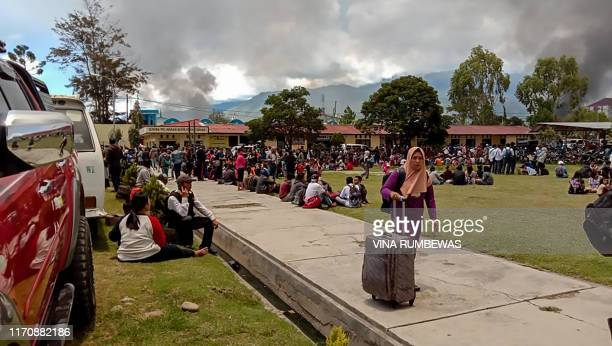 This picture taken on September 24, 2019 shows fleeing residents gathering at a field in Wamena, Papua province, as riots broke out in the restive...