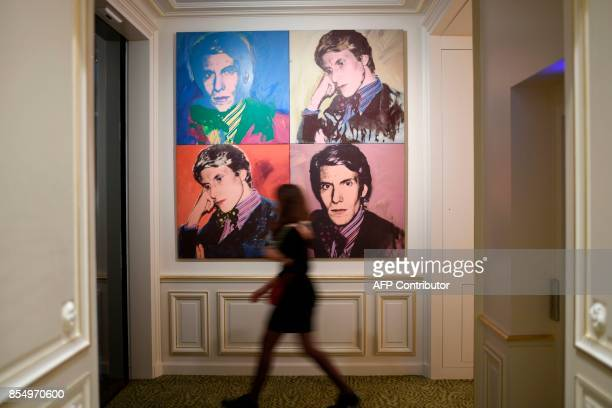 TOPSHOT This picture taken on September 25 2017 shows a woman walking past a reproduction of Andy Warhol's portrait of late French designer Yves...