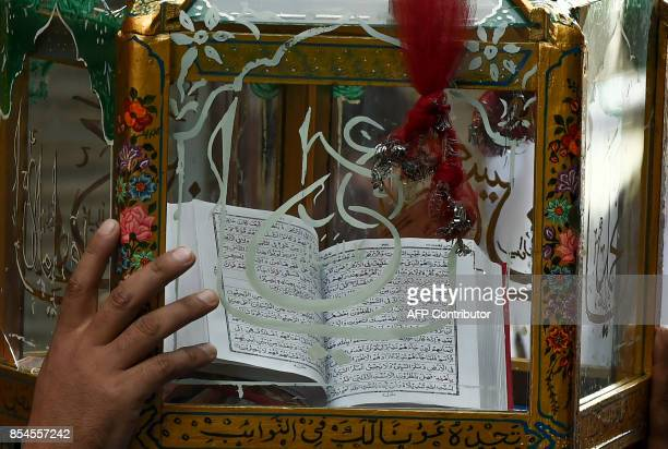 This picture taken on September 26 2017 shows an Indian Kashmiri mourner touching a glass case containing a copy of the Koran during a Shiite Muslim...