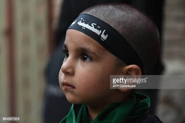This picture taken on September 26 2017 shows an Indian Kashmiri child watching devotees beat their chest during a Shiite Muslim procession held...