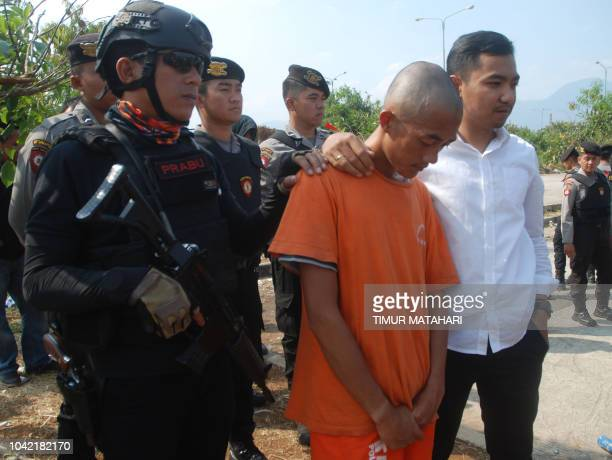 This picture taken on September 26 2018 shows Indonesian police escorting one of the suspects in the killing of Haringga Sirla a 23yearold Persija...