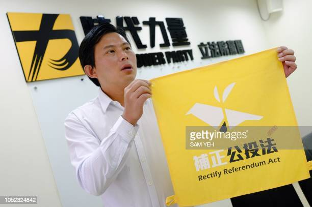 This picture taken on September 27 2018 shows Taiwan's New Power Party chairman and lawmaker Huang Kuochang displaying a flag during an interview in...