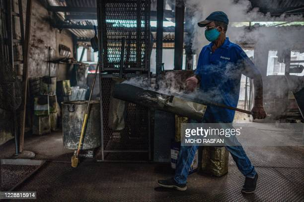 This picture taken on September 28 2020 shows a worker carrying wood fire roasted coffee beans at the Antong Coffee Factory in Taiping in the...