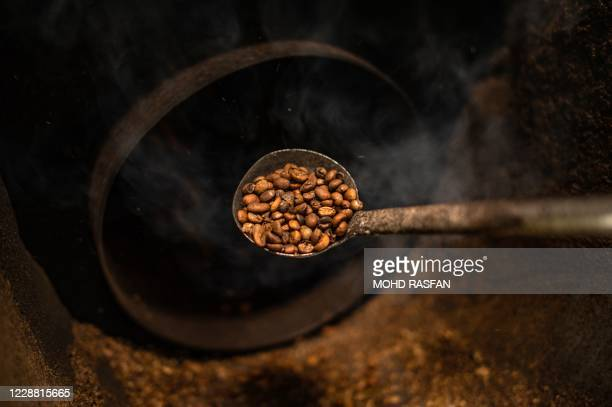 This picture taken on September 28 2020 shows a worker checking wood fire roasted coffee beans at the Antong Coffee Factory in Taiping in the...