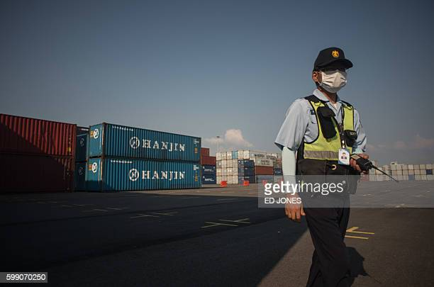 This picture taken on September 3 2016 shows a security guard walking before containers at the Hanjin Incheon Container Terminal in Seoul The...