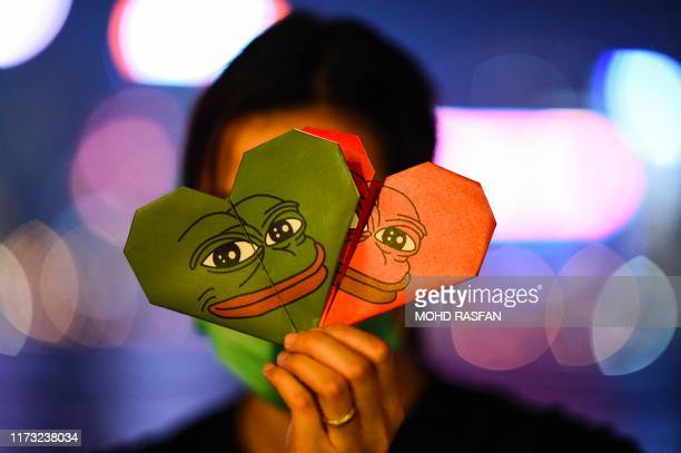 This picture taken on September 30, 2019 shows a protester holding origami hearts with a depiction of Pepe the Frog, a character used by...