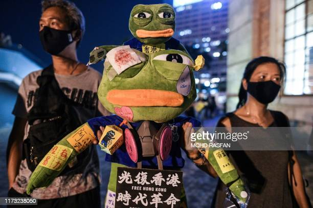 This picture taken on September 30 2019 shows protesters holding a stuffed toy depicting Pepe the Frog a character used by prodemocracy activists as...