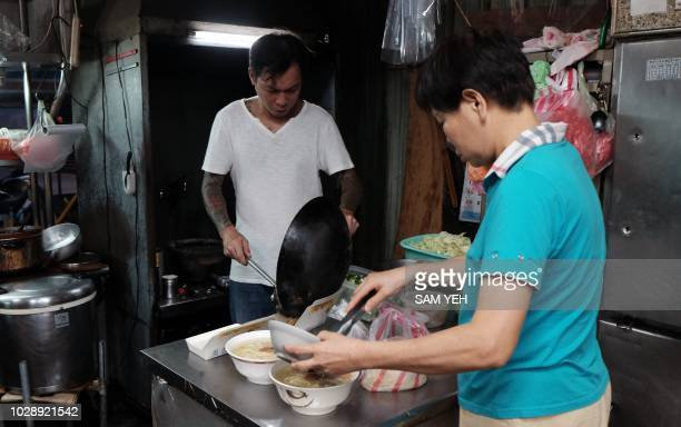 This picture taken on September 4 2018 show Yen Weishun a former criminal turned noodle shop owner for charity and his mother Yen Linyin cooking...