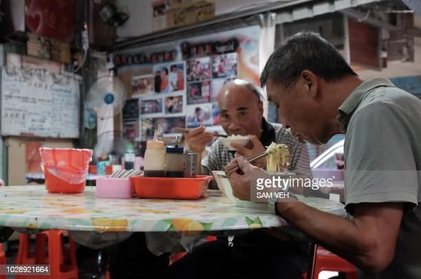 This picture taken on September 4 2018 shows two local residents eating free food at Yen Weishun a former criminal turned noodle shop owner for...