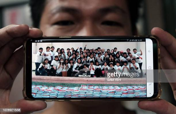 TOPSHOT This picture taken on September 4 2018 shows Yen Weishun a former criminal turned noodle shop owner for charity displaying a photo of himself...