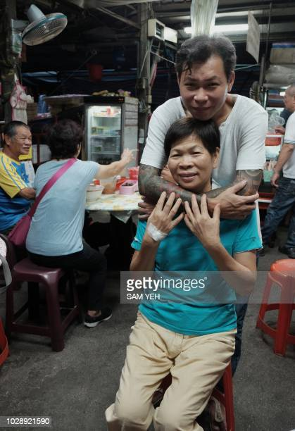 This picture taken on September 4 2018 shows Yen Weishun a former criminal turned noodle shop owner for charity hugging his mother Yen Linyin at...