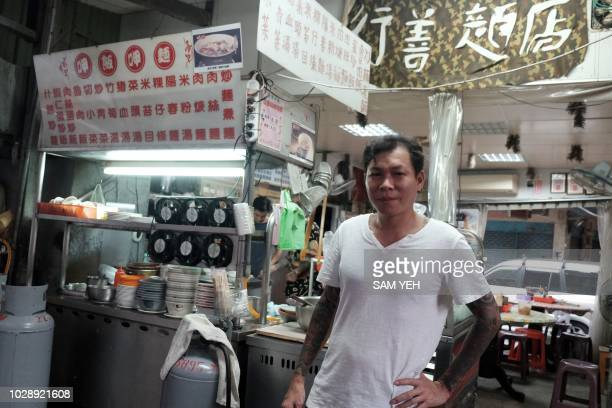 This picture taken on September 4 2018 shows Yen Weishun a former criminal turned noodle shop owner for charity posing for a photo in front of his...
