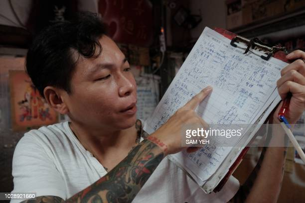 This picture taken on September 4 2018 shows Yen Weishun a former criminal turned noodle shop owner for charity displaying a list of charities at his...