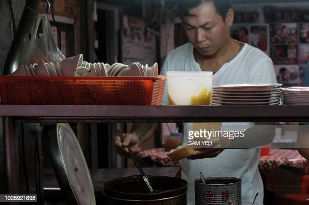 This picture taken on September 4 2018 shows Yen Weishun a former criminal turned noodle shop owner for charity preparing food at his noodle shop in...