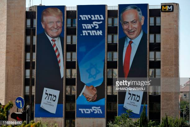 This picture taken on September 4 2019 shows an Israeli election banner for the Likud party showing US President Donald Trump shaking hands with...
