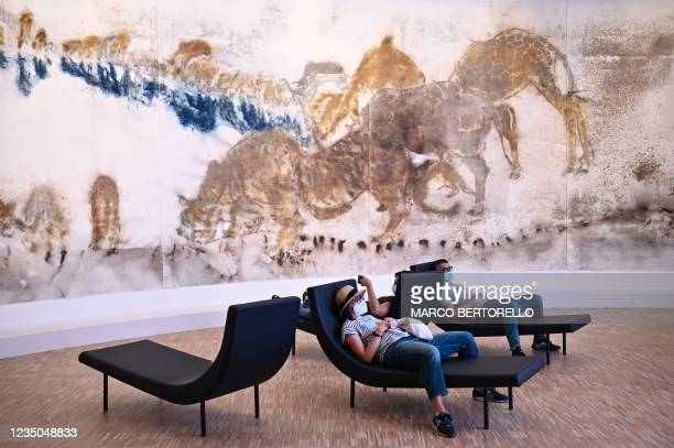 """This picture taken on September 4, 2021 shows people looking at """"White tone"""" by artist Cai Guo-Qiang displayed during the exhibition Les Citoyens by..."""