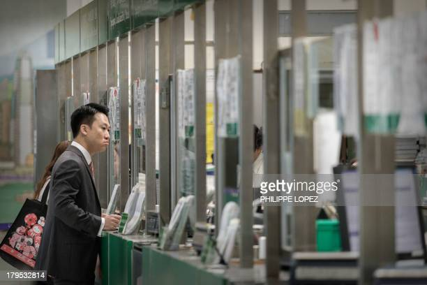This picture taken on September 5 2013 shows a man waiting at a counter of the General Post Office in Hong Kong AFP PHOTO / Philippe Lopez